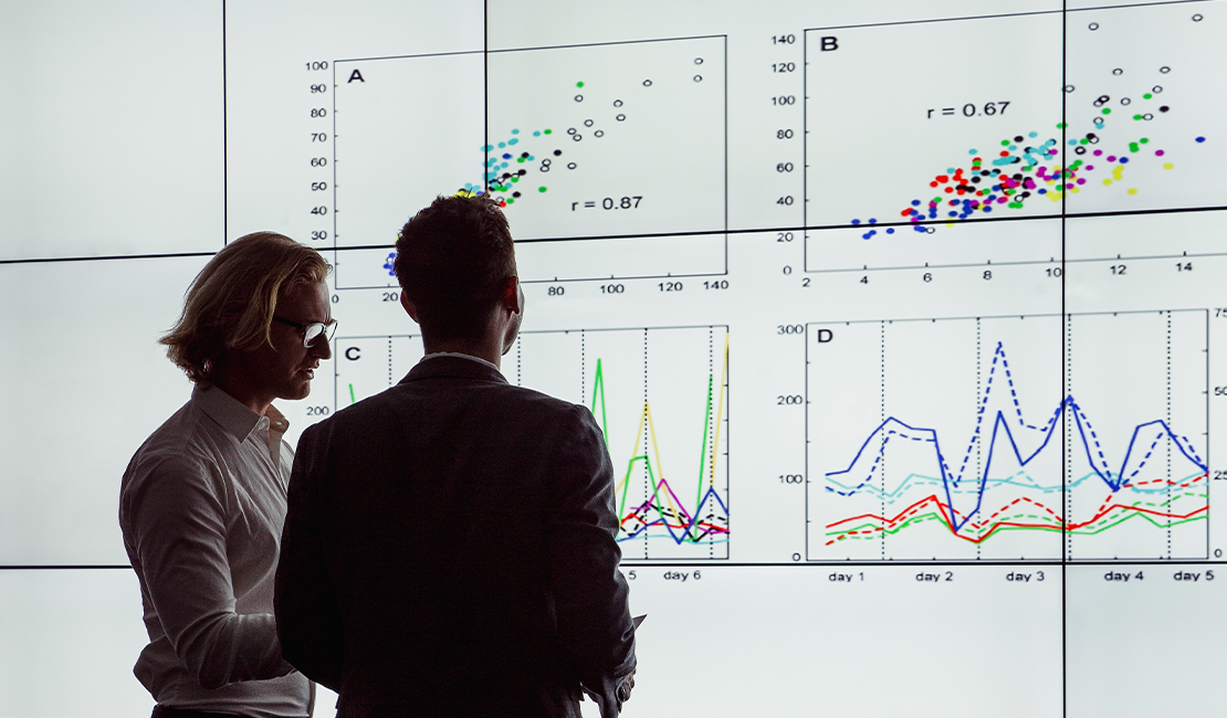 Two professionals analyze data projected on a screen in front of them.
